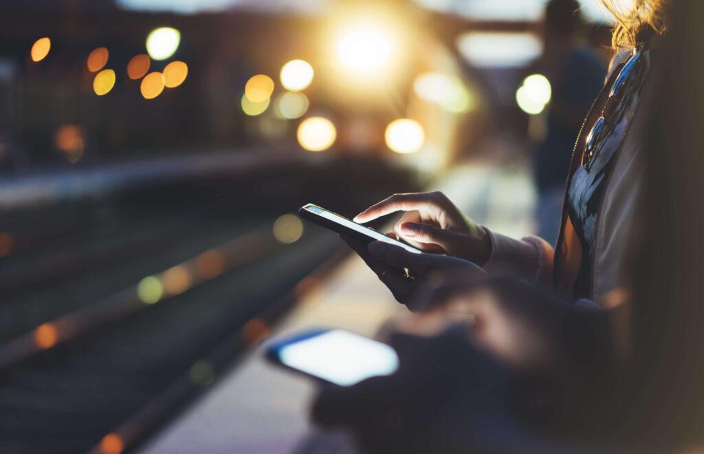 Deux personnes consultent leurs smartphones sur le quai d'une gare, de nuit. Le train arrive